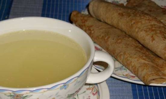 Transparent chicken broth with pancakes stuffed with porridge