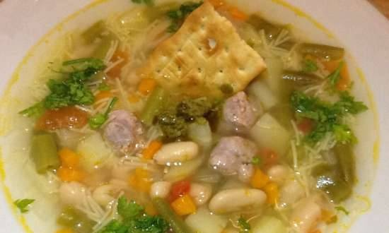 Italian vegetable soup with pasta, sausage meatballs and pesto sauce