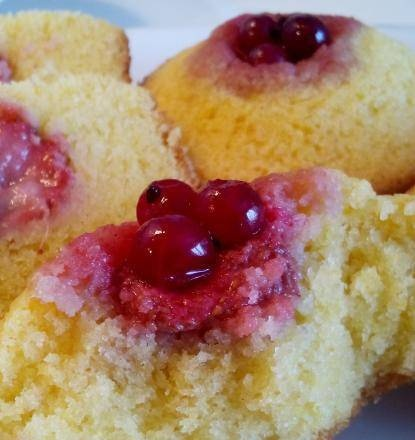 Sunny cupcakes with strawberries and red currants on corn flour