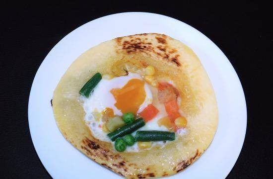 Fried eggs in zucchini with vegetables